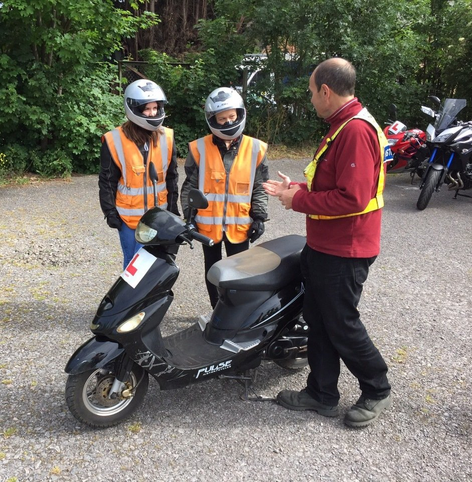Riding instructor explaining the controls of the moped