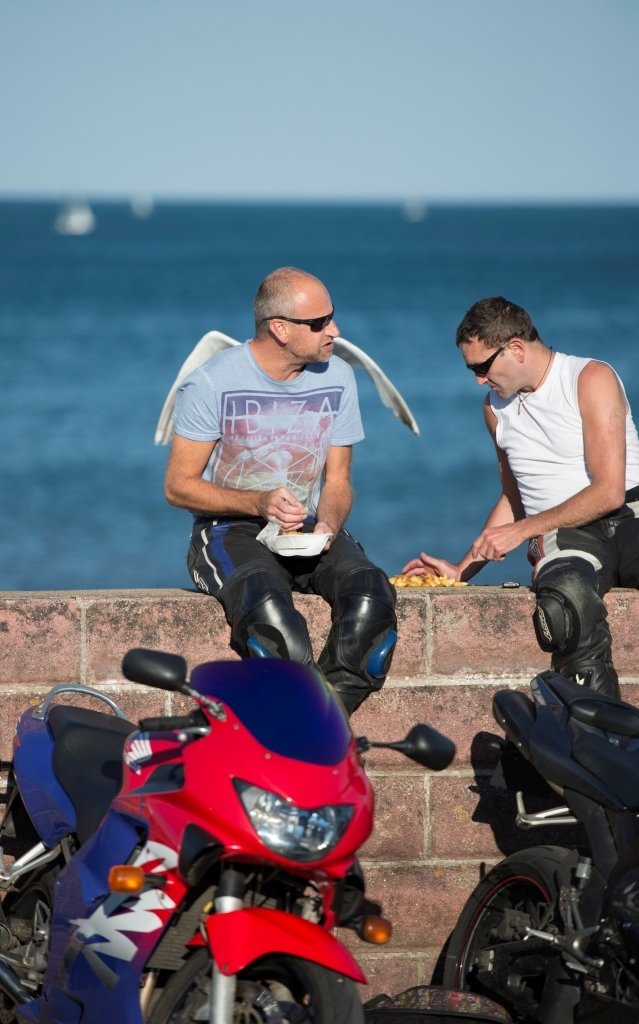 Two bikers eating chips